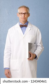 Health care professional looking to camera in lab coat bow tie and carrying clip board