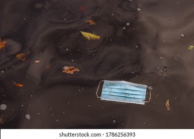 Health care and protection from virus concept, Light blue surgical face mask thrown away in water after used, Waste procedure or medical mask in canal of Amsterdam, Netherlands.