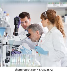 Health care researchers microscoping in life science laboratory. Young research scientists and senior professor preparing and analyzing microscope slides in research lab.