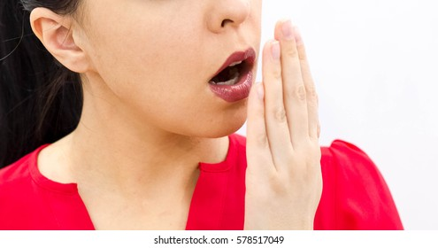 Health Care: Woman checking her breath with hand. Closeup portrait headshot sleepy young woman with wide open mouth Unrecognizable