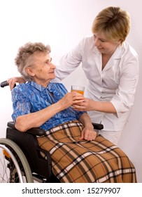 Health care worker and elderly woman in wheelchair needs help