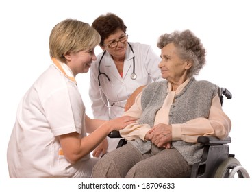 Health care workers and elderly woman in wheelchair