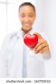 health and charity concept - close up of woman hand holding heart