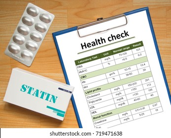 Health check report chart showing high blood cholesterol with generic pack of statins tablets for treatment dyslipidemia on wood table. Health care and medical concept. Top view.