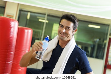 health club: athlete relaxing and drinking some water