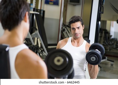health club: guy in a gym doing weight lifting at the mirror