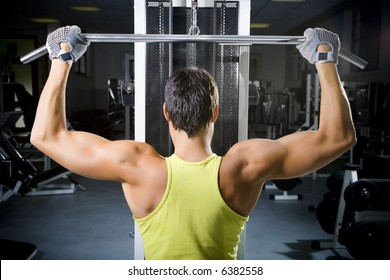 health club: man in a gym doing weight lifting
