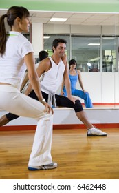 health club: man and women doing stretching and aerobics