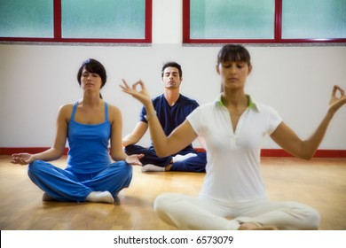 health club: man and women doing yoga