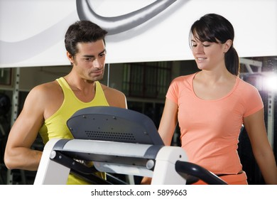 health club: woman walking on a tapis roulant with her personal trainer