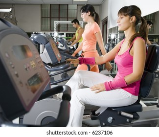 health club: women in the gym with their personal trainer