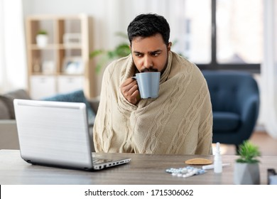 health, cold and people concept - sick young indian man in blanket with laptop computer drinking hot tea and working at home