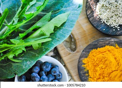 Health collage of leafy greens and super foods including collard greens, dandelion greens hemp seeds, antioxidant blueberries and anti-inflammatory turmeric on stones and a rustic wood cutting board.