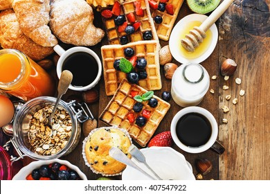 Health and colorful breakfast - cups of coffee with homemade granola, waffles, muffins,almond,hazelnuts,various fresh fruits, berries and milk on old wooden table. Health food concept  .Top view.