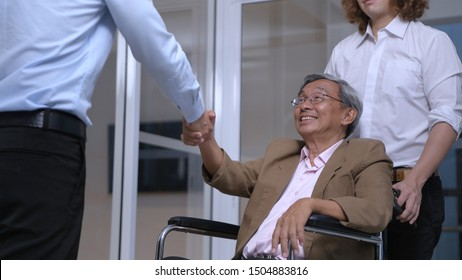 Health concept. The doctor is holding hands with the patient sitting on a wheelchair. 4k Resolution.