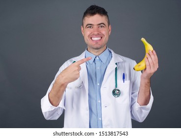 Health concept. Handsome doctor man wearing medical uniform, has board smile holds a fresh banana on his hand and pointing at it.