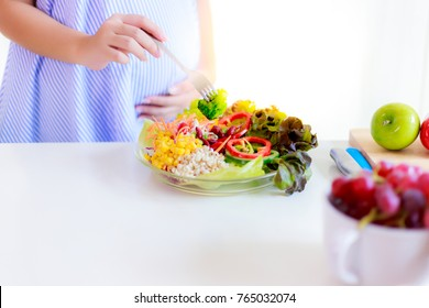 Health concept: A pregnant girl is using a fork to get broccoli for eating in the salad dish. It is healthy food for mother or pregnant . A mom cares or concerns her baby so much with copy space