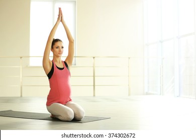 Health concept. Young beautiful pregnant woman does yoga exercise, close up