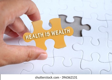 Health conceptual, hand holding puzzle written HEALTH IS WEALTH