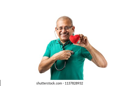Health conscious Indian/asian senior male adult checking heart beats with stethoscope, holding toy heart or apple in other hand, showing ok sign