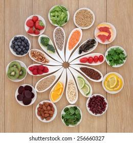 Health detox super food selection in porcelain bowls over oak wood background