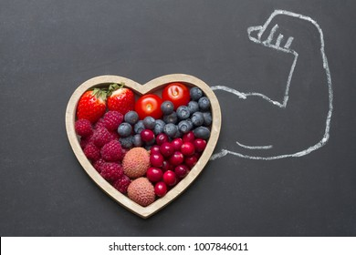 Health diet heart abstract concept with strongman hand on blackboard