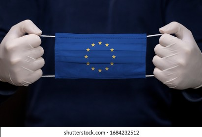 Health employee doctor holding medical face mask with the EU (European Union) flag. Coronavirus (COVID-19) pandemic affects the country.