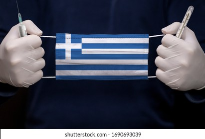 Health employee doctor holding syringe, mercury thermometer and medical face mask with Greece flag. Coronavirus (COVID-19) pandemic affects the country.