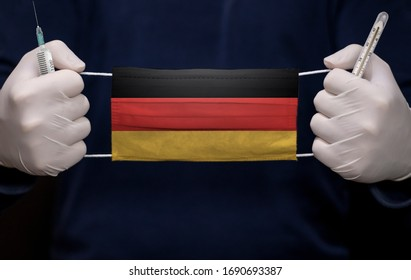 Health employee doctor holding syringe, mercury thermometer and medical face mask with Germany flag. Coronavirus (COVID-19) pandemic affects the country.