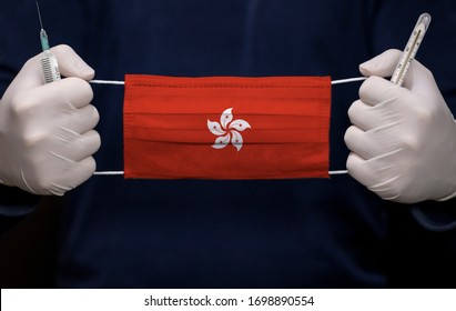 Health employee doctor holding syringe, mercury thermometer and medical face mask with Hong Kong flag. Coronavirus (COVID-19) pandemic affects the country.