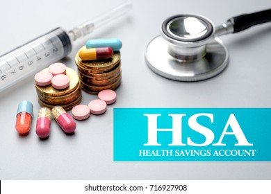 Health Financial concept of HSA Health Savings Account.Stethoscope, syringe, pills and stacked of coins on grey background. Selective focus image.