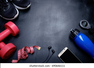 Health fitness background. Dumbbell, sneakers, measuring tape, phone, stopwatch, earphone and water bottle on dark background.