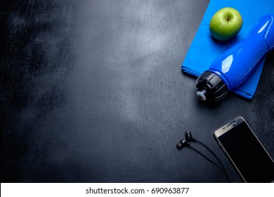 Health fitness background. Green apple. water bottle, blue towel, phone and earphone on dark background.