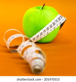 Health and fitness composition.Green apple against orange background.