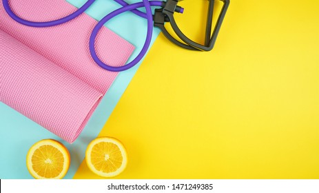 Health and fitness concept flatlay with exercise equipment on modern colorful background with copy space.