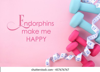 Health and fitness concept with pink and blue dumbbells and accessories on a pink wood table, with copy space, with Endorphins make me happy, text.