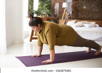 Health, fitness and sports concept. Plus size young brunette woman doing plank exercise on mat in cozy bedroom interior, going to loose extra pounds, become strong and fit, training endurance