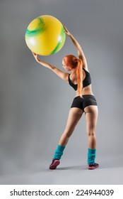 Health and Fitness woman in gym outfit with a Pilates ball doing exercises