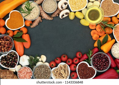 Health food  background border with fruit, vegetables, grains, pulses, herbs, spices, seeds, nuts, himalayan salt and olive oil. Food high in antioxidants,  smart carbohydrates, vitamins and minerals.