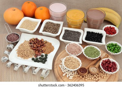 Health food for body builders with supplement powders, vitamin tablets, pulses, nuts, vegetables, fruit and smoothie juice shakes with tape measure.