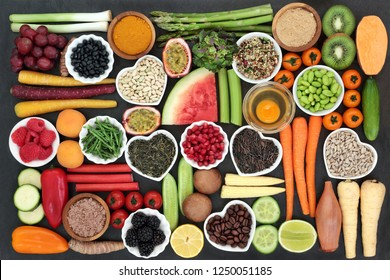 Health food for clean eating concept including grains, seeds, coffee, supplement powders, fresh fruit, vegetables and dairy. High in antioxidants, protein, anthocyanins, vitamins and dietary fibre.