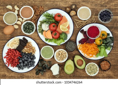 Health food concept to boost brain power and promote memory with fish, fruit, vegetables, nuts, seeds, herbs, supplement powders and tablets on rustic wood background. Top view.