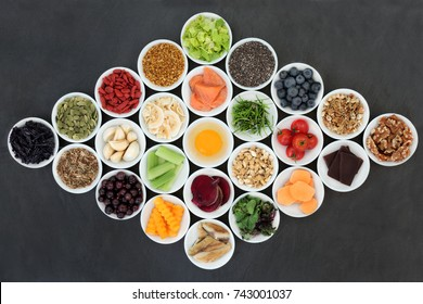 Health food concept to boost brain power and promote memory in porcelain bowls on slate background. Foods high in antioxidants, anthocyanins, vitamins and minerals.