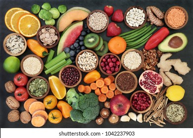 Health food concept with fruit, vegetables, seeds, pulses, grains, cereals, herbs and spices with foods high in vitamins, minerals, anthocyanins, antioxidants and fibre on slate background top view.