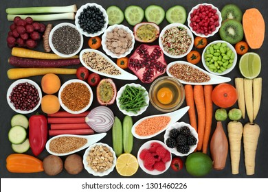 Health food for fitness  concept with dairy, fresh fruit, vegetables, grains, cereal, seeds, pollen grain, herbs and spice. High in antioxidants, protein, anthocyanins, vitamins and dietary fibre.