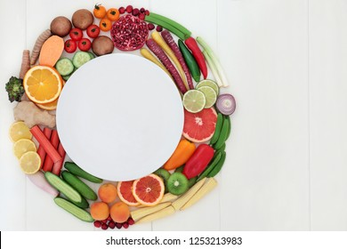 Health food for fitness concept with fresh fruit, vegetables and spices with super foods very high in antioxidants, protein, anthocyanins, vitamins and dietary fibre. Top view on white wood.