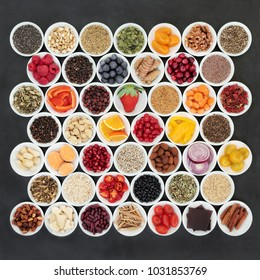 Health food for a healthy heart with chinese and ayurvedic herbal medicine, vegetables, fruit, nuts, seeds, pulses, cereals and grains and herbs on  slate. High in omega 3, antioxidants & anthocyanins