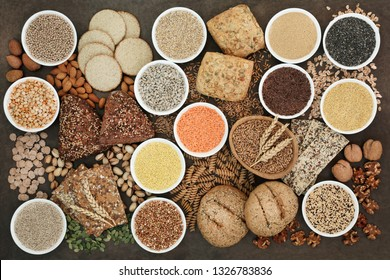 Health food for a high fibre diet with legumes, whole grain bread rolls, whole wheat pasta, seeds, nuts, grain and cereals on lokta paper background. High in antioxidants, vitamins and minerals.