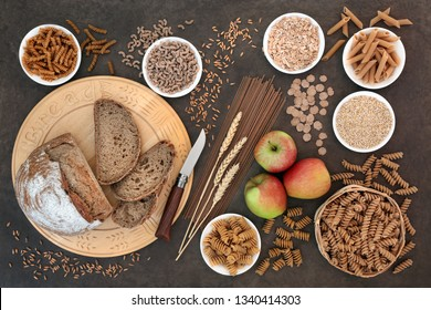 Health food for a high fibre diet with apples, whole grain rye bread, whole wheat pasta, oatmeal, oats, bran flakes and wheat sheath. High in vitamins, smart carbs, antioxidants and minerals.
