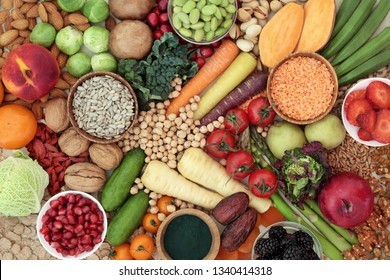 Health food for a high fibre diet concept with fruit, vegetables, whole grain bread, grains, legumes, nuts, grains, seeds, spirulina and cereals. Foods with antioxidants, anthocyanins & vitamins.